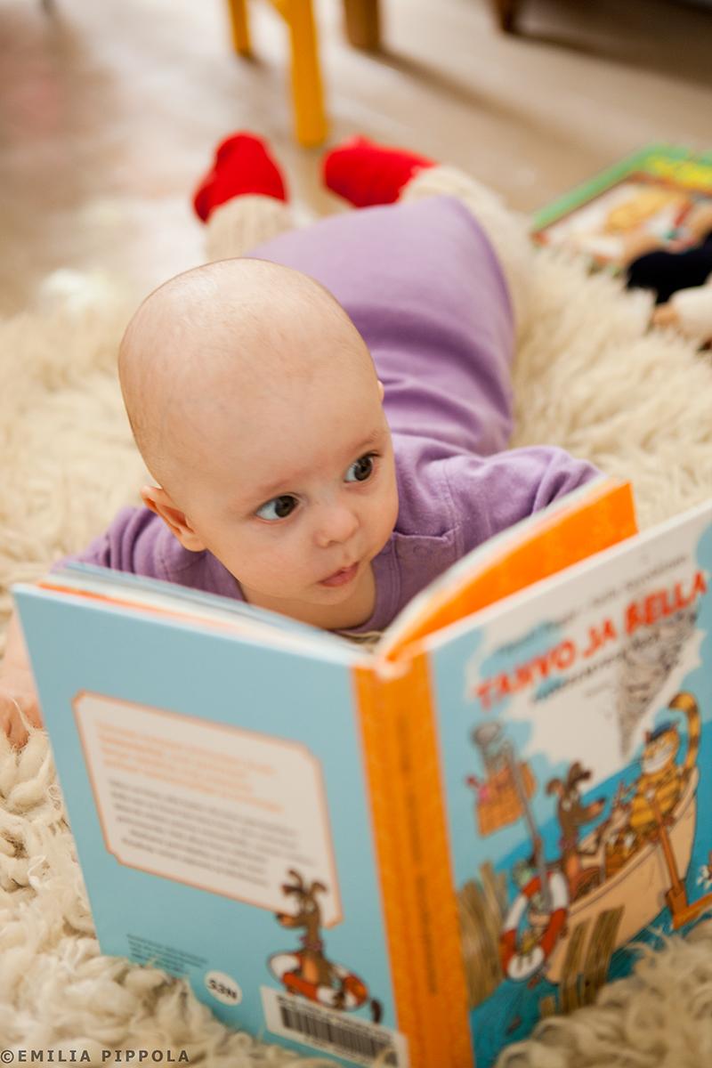 Uoti-vauva katselee kirjan kuvia